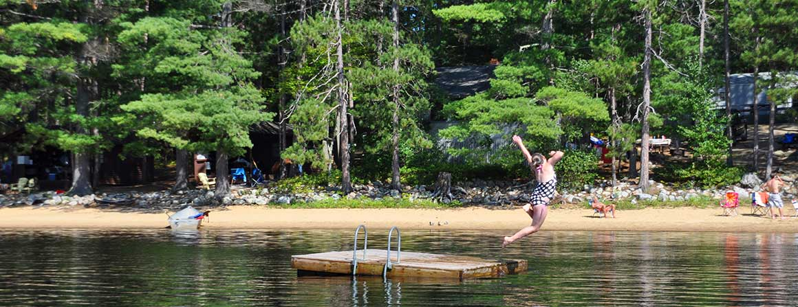Girl jumping off the dock in the lake at Papoose Pond Campground
