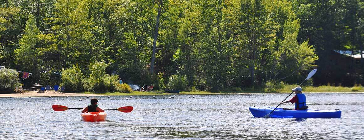 Family kayaking on the lake at Papoose Pond Camp