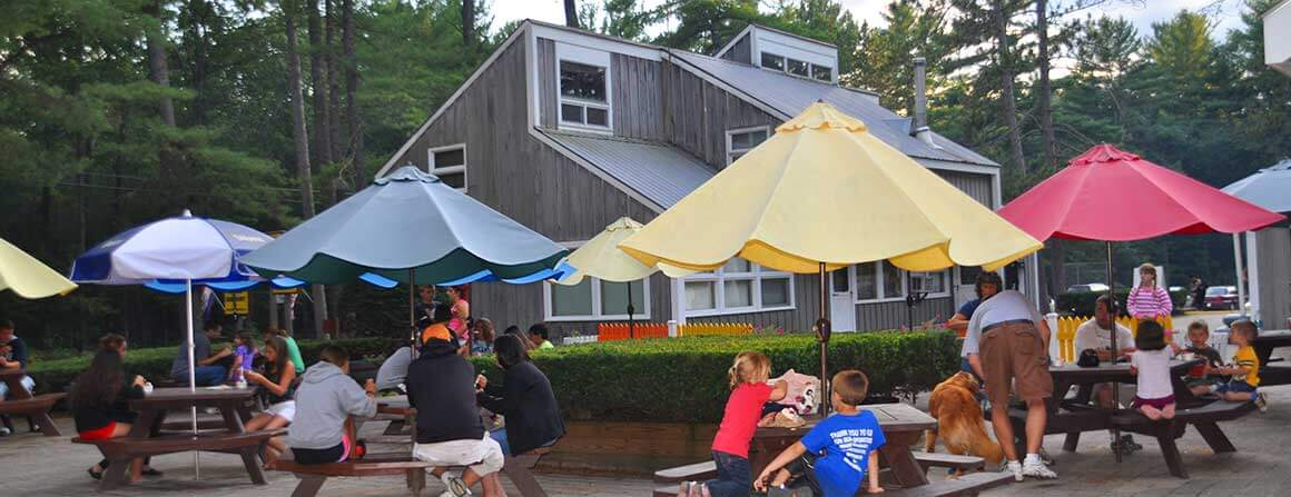 Families eating at picnic tables at the Papoose Pond Camp plaza
